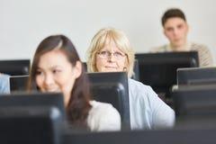Ανώτερη γυναίκα στη σειρά μαθημάτων υπολογιστών στοκ εικόνες