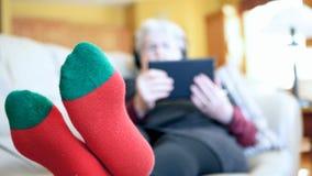 Ανώτερη γυναίκα στις κόκκινες κάλτσες που χαλαρώνει στον καναπέ στο σπίτι με την ταμπλέτα και τα ακουστικά Γιαγιά που διαβάζει κα φιλμ μικρού μήκους