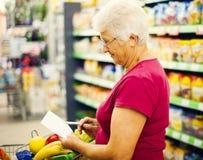 Ανώτερη γυναίκα στο κατάστημα παντοπωλείων στοκ εικόνες