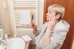 Ανώτερη γυναίκα σχετικά με το μαλακό δέρμα και να φανεί προσώπου της διαθέσιμος καθρέφτης χεριών στο σπίτι στοκ εικόνες με δικαίωμα ελεύθερης χρήσης