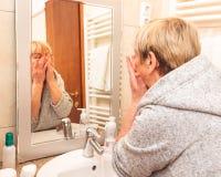 Ανώτερη γυναίκα σχετικά με το μαλακό δέρμα προσώπου της, που κοιτάζει στον καθρέφτη στο σπίτι στοκ φωτογραφία με δικαίωμα ελεύθερης χρήσης