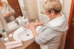 Ανώτερη γυναίκα σχετικά με το μαλακό δέρμα προσώπου της, που κοιτάζει στον καθρέφτη στο σπίτι στοκ εικόνες με δικαίωμα ελεύθερης χρήσης