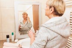 Ανώτερη γυναίκα σχετικά με το μαλακό δέρμα προσώπου της, που κοιτάζει στον καθρέφτη στο σπίτι στοκ εικόνα με δικαίωμα ελεύθερης χρήσης