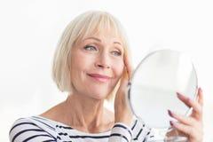 Ανώτερη γυναίκα σχετικά με το μαλακό δέρμα προσώπου της στοκ εικόνες