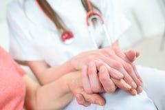 Ανώτερη γυναίκα χεριών εκμετάλλευσης νοσοκόμων στην καρέκλα ροδών στοκ εικόνες