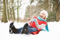 Ανώτερη γυναίκα Sledging μέσω της χιονώδους δασώδους περιοχής στοκ φωτογραφία