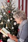 Ανώτερη γυναικεία ανάγνωση μπροστά από το χριστουγεννιάτικο δέντρο Στοκ Φωτογραφία