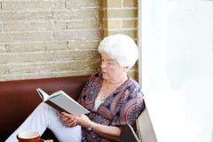 Ανώτερη γυναικεία ανάγνωση στη καφετερία Στοκ Εικόνες