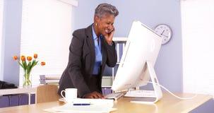 Ανώτερη επιχειρηματίας που μιλούν στο τηλέφωνο και εργασία στην αρχή Στοκ Εικόνα
