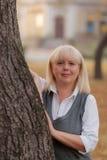 Ανώτερη επιχειρησιακή γυναίκα που περπατά στο πάρκο φθινοπώρου Μια γυναίκα σε ένα κλασικό ύφος ιματισμού Κομψή γυναίκα σε ένα κοσ Στοκ Εικόνα