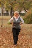 Ανώτερη επιχειρησιακή γυναίκα που περπατά στο πάρκο φθινοπώρου Μια γυναίκα σε ένα κλασικό ύφος ιματισμού Κομψή γυναίκα σε ένα κοσ Στοκ Φωτογραφία