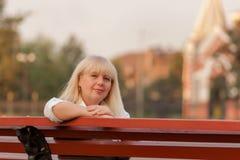 Ανώτερη επιχειρησιακή γυναίκα που περπατά στο πάρκο φθινοπώρου Μια γυναίκα σε ένα κλασικό ύφος ιματισμού Κομψή γυναίκα σε ένα κοσ Στοκ Εικόνες