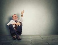 Ανώτερη ευτυχής συνεδρίαση ατόμων στο πάτωμα με τα πόδια που διασχίζονται και που δείχνουν επάνω Στοκ Εικόνες