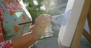 Ανώτερη ζωγραφική γυναικών στον καμβά στον κήπο 4k απόθεμα βίντεο