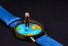 Ανώτερη ηλικία backpacker και ρολόγια παγκόσμιων χαρτών Γύρω από το έμβλημα φωτογραφιών παγκόσμιου ταξιδιού Στοκ Εικόνα