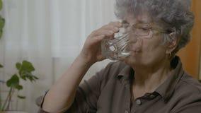 Ανώτερη ηλικιωμένη γυναίκα που παίρνει ένα χάπι που καταπίνει και που πίνει ολόκληρο ένα ποτήρι του νερού μετά από το - απόθεμα βίντεο