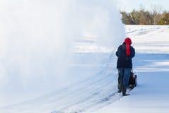 Ανώτερη κίνηση καθαρίσματος γυναικών με snowblower Στοκ Φωτογραφίες