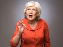 Ανώτερη κυρία που παρουσιάζει εντάξει σημάδι Στοκ Φωτογραφίες