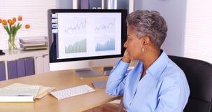Ανώτερη μαύρη επιχειρησιακή γυναίκα που μιλά στο τηλέφωνο από τον υπολογιστή Στοκ Εικόνα