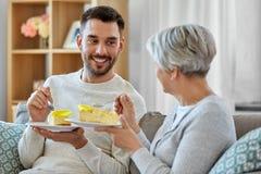 Ανώτερη μητέρα και ενήλικος γιος που τρώνε το κέικ στο σπίτι στοκ φωτογραφίες