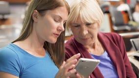 Ανώτερη μητέρα και η νέα συνεδρίαση κορών της στο τερματικό αερολιμένων που περιμένει την πτήση που χρησιμοποιεί το smartphone απόθεμα βίντεο