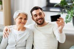 Ανώτερη μητέρα με την ενήλικη λήψη γιων selfie στο σπίτι στοκ εικόνες