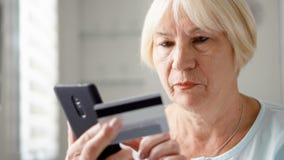 Ανώτερη συνεδρίαση γυναικών στο σπίτι Να ψωνίσει on-line με την πιστωτική κάρτα στο smartphone Τεχνολογία και ηλικιωμένοι απόθεμα βίντεο
