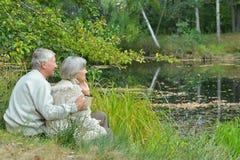 Ανώτερη συνεδρίαση ζευγών στο πάρκο κοντά στη λίμνη Στοκ εικόνες με δικαίωμα ελεύθερης χρήσης