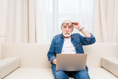 Ανώτερη συνεδρίαση ατόμων με το lap-top στα γόνατα και eyeglasses εκμετάλλευσης Στοκ φωτογραφία με δικαίωμα ελεύθερης χρήσης
