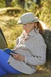 Ανώτερη συνεδρίαση γυναικών που διαβάζει υπαίθρια ένα βιβλίο Στοκ Φωτογραφία