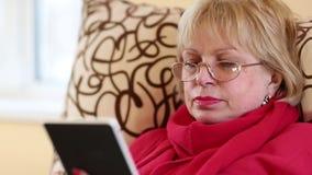 Ανώτερη συνεδρίαση γυναικών σε έναν καναπέ και χρησιμοποίηση του ηλεκτρονικού βιβλίου απόθεμα βίντεο