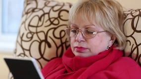Ανώτερη συνεδρίαση γυναικών σε έναν καναπέ και χρησιμοποίηση του ηλεκτρονικού βιβλίου Γυναίκα με το eBook απόθεμα βίντεο