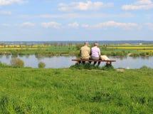 Ανώτερη συνεδρίαση ζευγών στην όχθη ποταμού Στοκ φωτογραφία με δικαίωμα ελεύθερης χρήσης