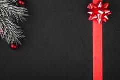 Ανώτερη τοπ άποψη μιας κόκκινης κορδέλλας και ενός αειθαλούς κλάδου σε ένα μαύρο υπόβαθρο πετρών Στοκ εικόνες με δικαίωμα ελεύθερης χρήσης