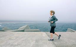 Ανώτερη φίλαθλος με το τρέξιμο ακουστικών Στοκ Εικόνες