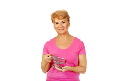 Ανώτερη χαμογελώντας γυναίκα που κρατά το μικρό καροτσάκι Στοκ φωτογραφία με δικαίωμα ελεύθερης χρήσης