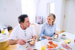 Ανώτεροι άνδρας και γυναίκα που έχουν το ηλιόλουστο πρωί προγευμάτων Στοκ φωτογραφία με δικαίωμα ελεύθερης χρήσης