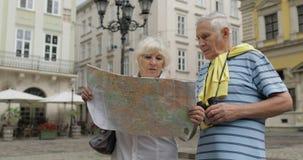 Ανώτεροι αρσενικοί και θηλυκοί τουρίστες που περπατούν με έναν χάρτη στα χέρια που ψάχνουν τη διαδρομή απόθεμα βίντεο