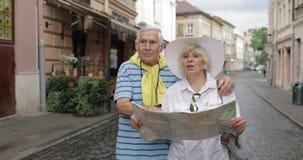 Ανώτεροι αρσενικοί και θηλυκοί τουρίστες που στέκονται με έναν χάρτη στα χέρια που ψάχνουν τη διαδρομή απόθεμα βίντεο