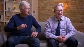 Ανώτεροι αρσενικοί φίλοι που κάθονται μαζί στον καναπέ που προσέχει προσεκτικά το ποδόσφαιρο στη TV και που συζητά ενεργά και χαρ απόθεμα βίντεο