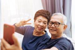 Ανώτεροι ασιατικοί παππούδες και γιαγιάδες ζευγών που παίρνουν μια φωτογραφία selfie μαζί στο σπίτι στοκ φωτογραφίες με δικαίωμα ελεύθερης χρήσης