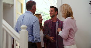 Ανώτεροι γονείς που καλωσορίζουν τα επισκεπτόμενα ενήλικα παιδιά στη μπροστινή πόρτα απόθεμα βίντεο