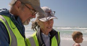 Ανώτεροι εθελοντές που αλληλεπιδρούν ο ένας με τον άλλον στην παραλία 4k απόθεμα βίντεο
