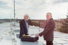 Ανώτεροι επιχειρηματίες που κάνουν μια επιχείρηση να ασχοληθεί στη στέγη μιας κατασκευής Στοκ φωτογραφία με δικαίωμα ελεύθερης χρήσης