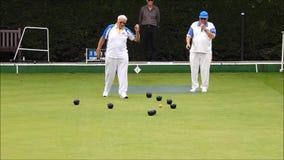 Ανώτεροι συνταξιούχοι μελών oap που παίζουν τα κύπελλα που κυλούν τον πράσινο υπαίθρια ενεργό αθλητισμό απόθεμα βίντεο