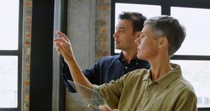 Ανώτεροι υπάλληλοι που συζητούν πέρα από τον πίνακα γυαλιού 4k φιλμ μικρού μήκους