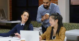 Ανώτεροι υπάλληλοι που συζητούν πέρα από το lap-top στην καφετέρια γραφείων 4k απόθεμα βίντεο