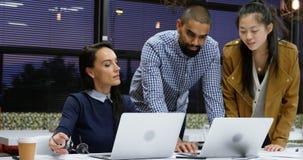Ανώτεροι υπάλληλοι που συζητούν πέρα από το lap-top στον πίνακα 4k απόθεμα βίντεο