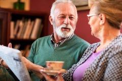 Ανώτεροι φίλοι που μιλούν, που διαβάζουν την εφημερίδα και που το τσάι στο ho Στοκ Φωτογραφία