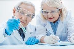Ανώτεροι φαρμακοποιοί που εξετάζουν τις σημειώσεις σωλήνων δοκιμής και γραψίματος Στοκ Εικόνες
